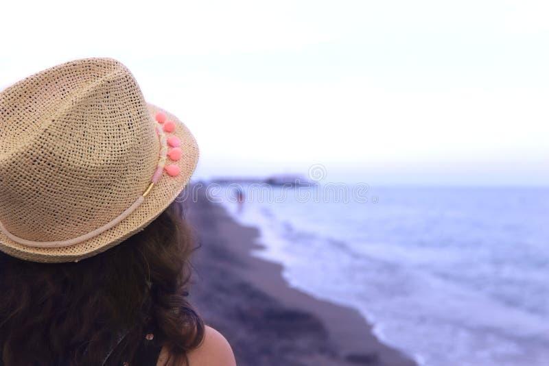 En flicka i en sugr?rhatt ser horisontlinjen vid havet p? stranden arkivfoton