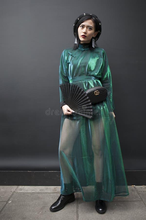 En flicka i en svart basker, en grön genomskinlig klänning, svarta kortslutningar royaltyfria bilder