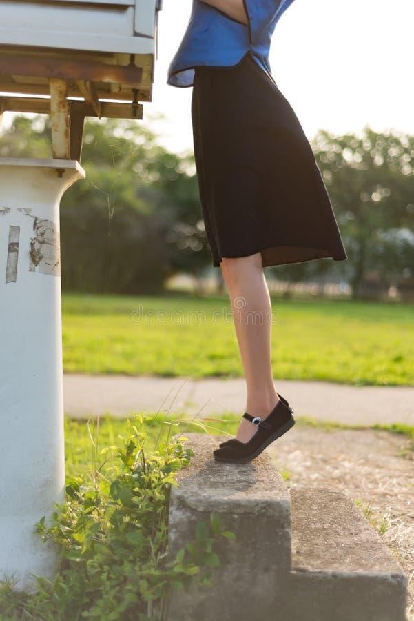 En flicka i en svart kjol valde upp hennes fot royaltyfri fotografi