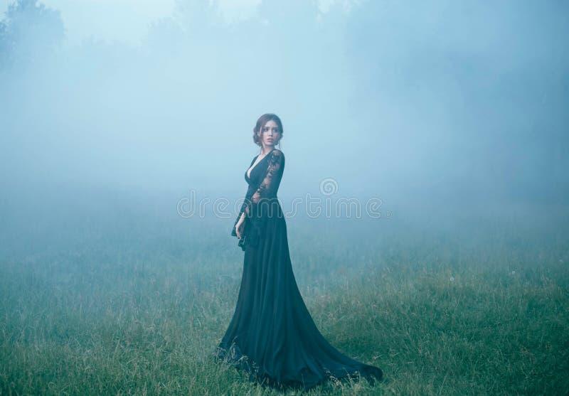En flicka i en svart lång klänning som promenerar ia en röjning i tjock dimma förskräckt härligt, häxaia som går till skogen royaltyfri fotografi