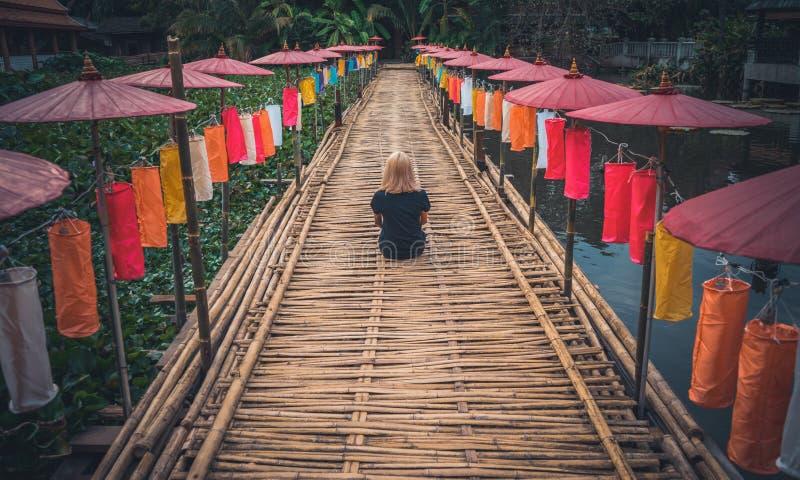 En flicka i en svart T-tröja sitter med henne tillbaka till kameran på en bambubana som dekoreras med ljusa thailändska paraplyer arkivbild
