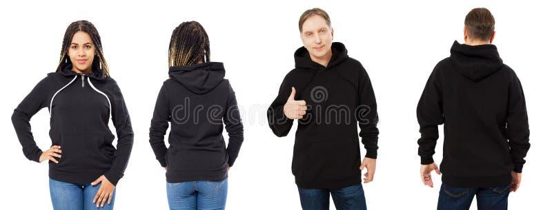 En flicka i en svart tröja med en huv och en man i en tröjaframdel och som isolerar tillbaka, tom hoodiemodell arkivfoton