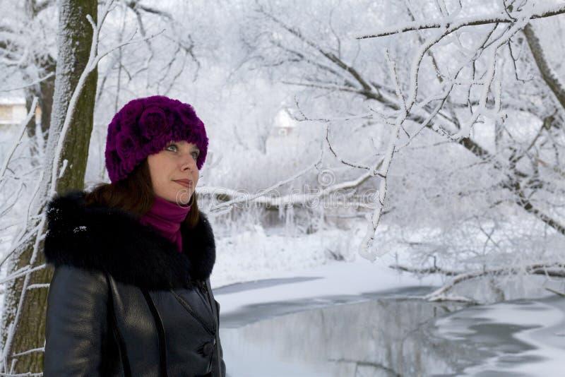 En flicka i vinterkläder som går till och med snö-täckt, parkerar Synlig isbunden flod arkivfoton