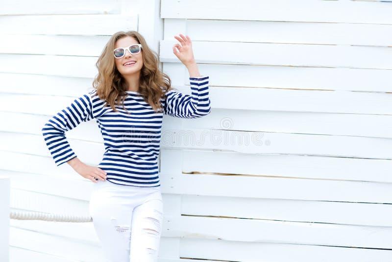 En flicka i vit åtsittande jeans och sportskor som poserar mot en vit trävägg I en sjömant-skjorta och exponeringsglas lockigt royaltyfria foton
