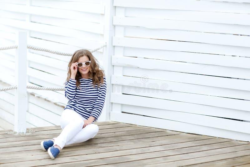 En flicka i vit åtsittande jeans och sportskor som poserar mot en vit trävägg I en sjömant-skjorta och exponeringsglas lockigt royaltyfri bild
