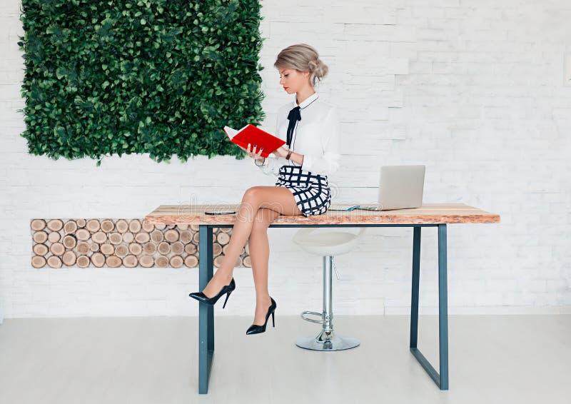 En flicka i en vit blus sitter på en tabell med en anteckningsbok royaltyfria foton