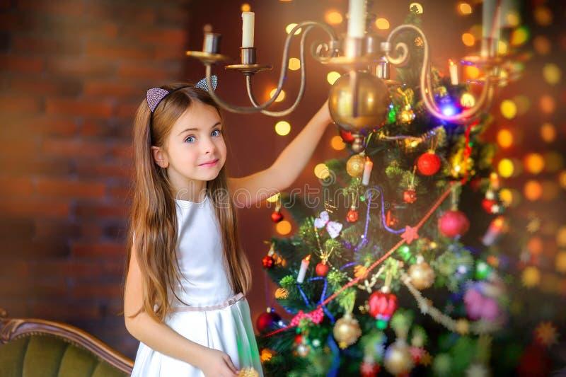 En flicka i en vit klänning dekorerar en festlig julgran royaltyfria bilder