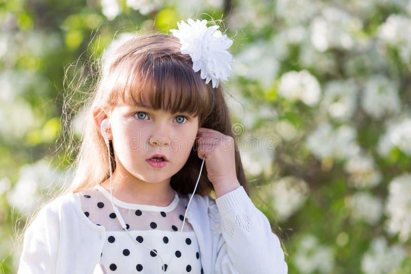 En flicka i en vit klänning lyssnar till musik till och med liten ljudsignal hörlurar arkivfoto