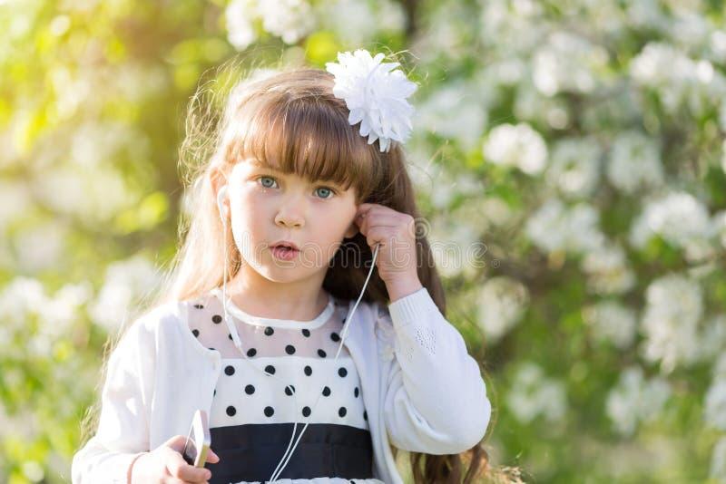 En flicka i en vit klänning lyssnar till musik till och med liten ljudsignal hörlurar arkivbild