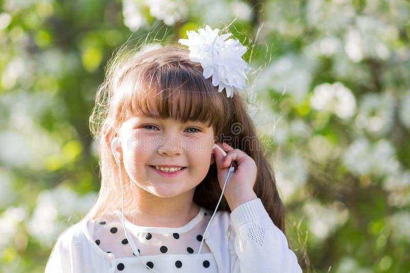 En flicka i en vit klänning lyssnar till musik till och med liten ljudsignal hörlurar royaltyfri foto