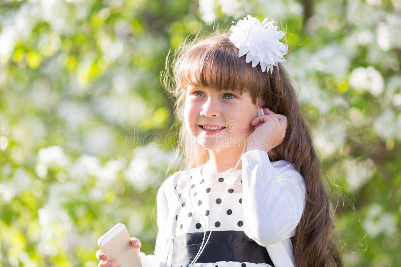 En flicka i en vit klänning lyssnar till musik till och med liten ljudsignal hörlurar fotografering för bildbyråer