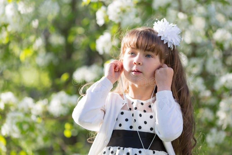 En flicka i en vit klänning lyssnar till musik till och med liten ljudsignal hörlurar arkivbilder