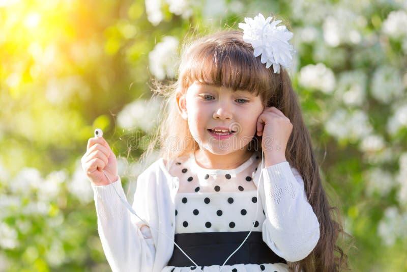 En flicka i en vit klänning lyssnar till musik till och med liten ljudsignal hörlurar royaltyfria bilder