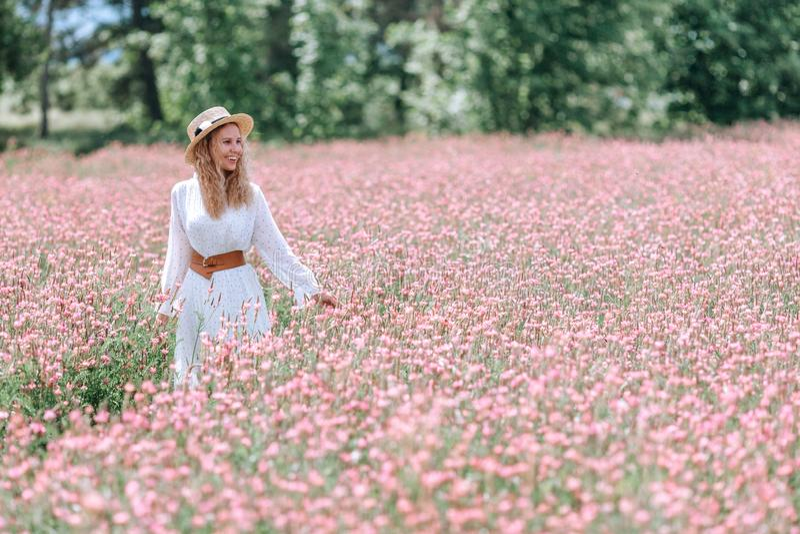 En flicka i en vit kl?nning med prickar och en hatt i ett blomma f?lt av sainfoin arkivbilder