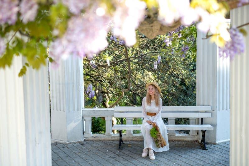 En flicka i en vit kl?nning och en sugr?rhatt tycker om blomningen av wisteriaen royaltyfria foton