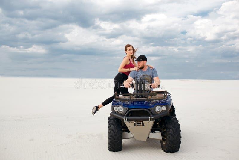 En flicka klättrar hennes pojkvän på en kvadratcykel, dem förbereder sig för en tur i öknen, ett stilfullt ungt par fotografering för bildbyråer