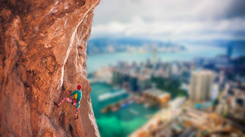 En flicka klättrar en klättrarutt royaltyfri foto