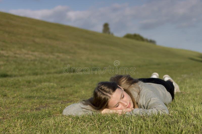 En flicka kopplas av på gräset och har hans ögon att stängas royaltyfri fotografi