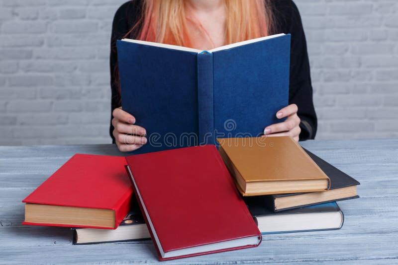 En flicka läser en bok bredvid en hög av andra spridda böcker lära för begrepp arkivfoton