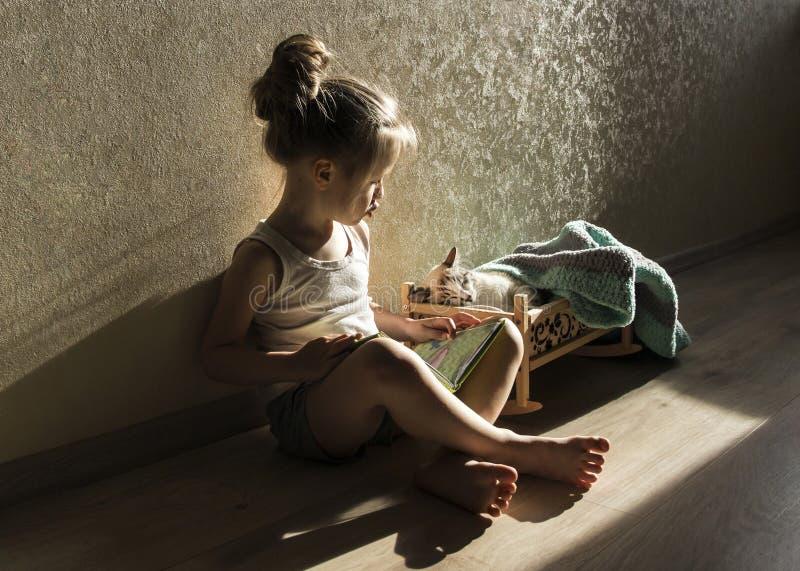 En flicka läser en saga från en bok till en katt i en lathund royaltyfria bilder
