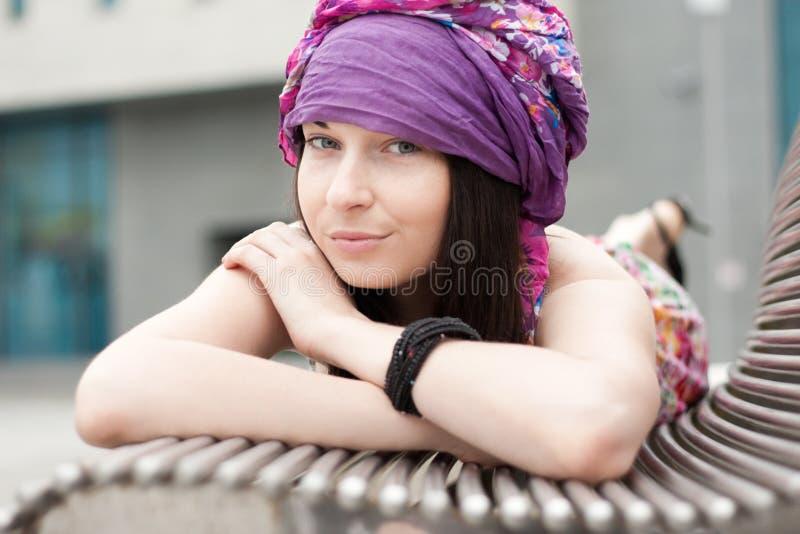 En flicka ligger på bänk royaltyfri bild