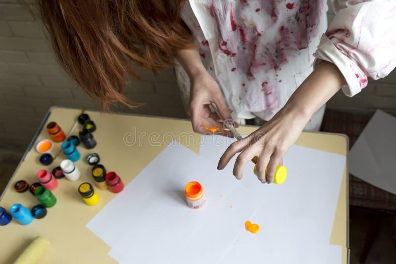 En flicka målar bilden med färger genom att använda hennes egna händer royaltyfria bilder