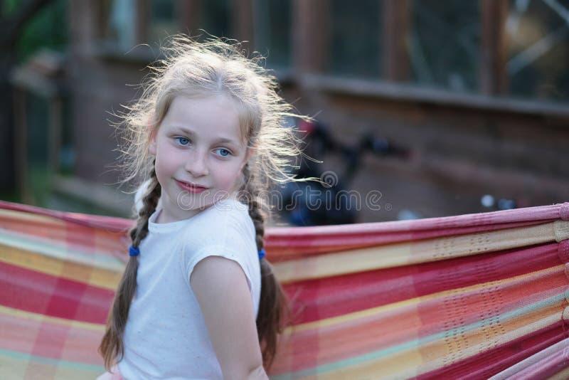 En flicka med blonda råttsvansar sitter i en hängmatta royaltyfri bild