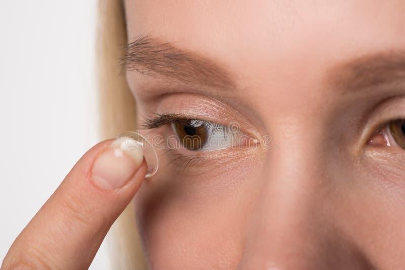 En flicka med bruna ögon bär en kontaktlins för vision arkivfoton
