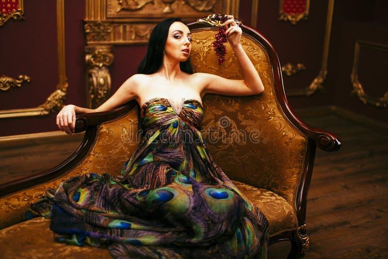 En flicka med druvor royaltyfria bilder