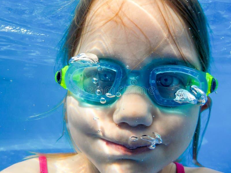En flicka med dykningskyddsglasögon dyker i pölen och rymmer hennes andedräkt fotografering för bildbyråer
