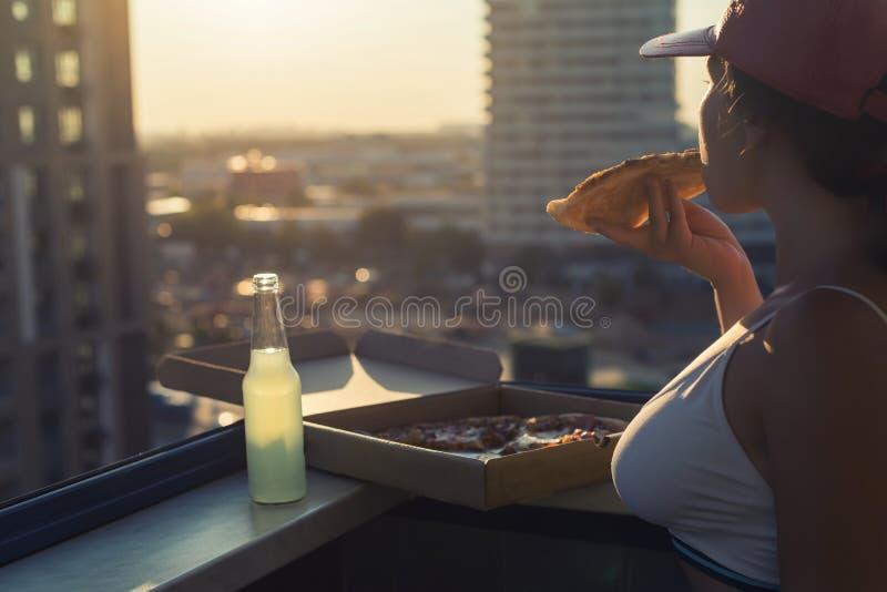 En flicka med ett härligt bröst i en sportdräkt äter pizza- och drinkmojito på solnedgångstadsbakgrunden arkivbilder
