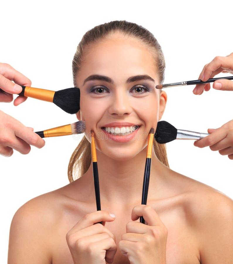 En flicka med ett leende sträckte med makeupborstar på en vit isolerad bakgrund royaltyfria bilder
