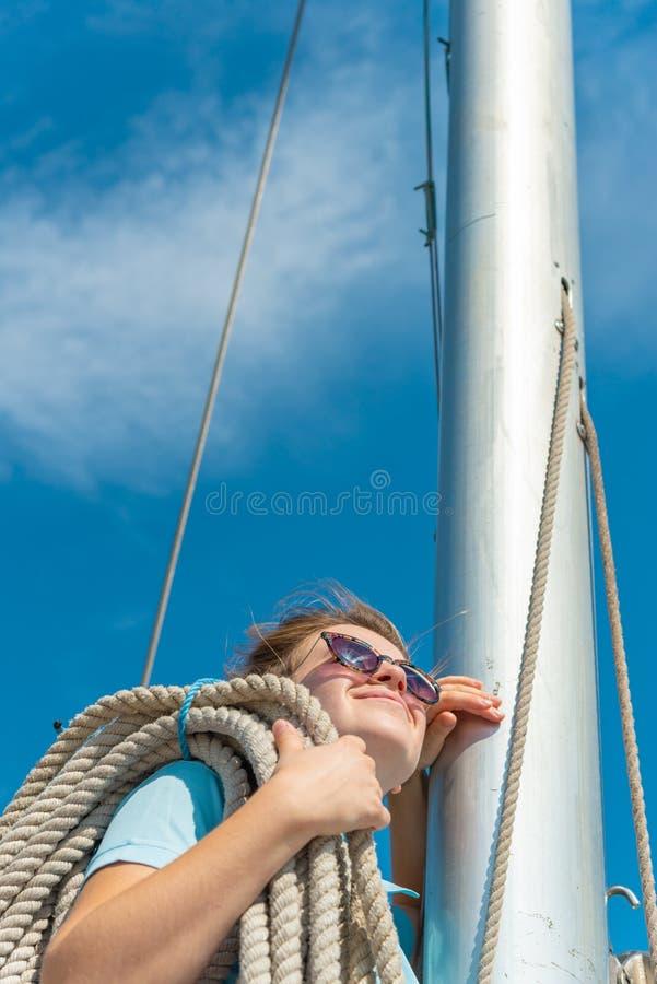 En flicka med ett rep på däcket av en yacht ser omkring och rymmer stammarna på hennes skuldra arkivbilder