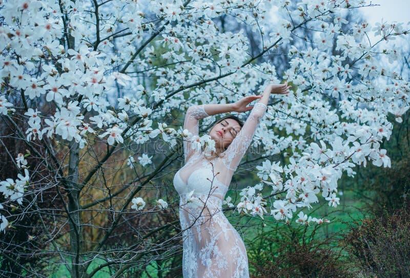 En flicka med ganska hår, i en genomskinlig dressing-kappa som poserar mot en bakgrund av att blomma, vit magnolia Vår försiktig  royaltyfria bilder