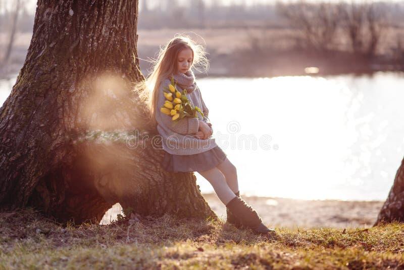 En flicka med gula tulpan i tidig vår på en kall afton nära floden arkivfoton