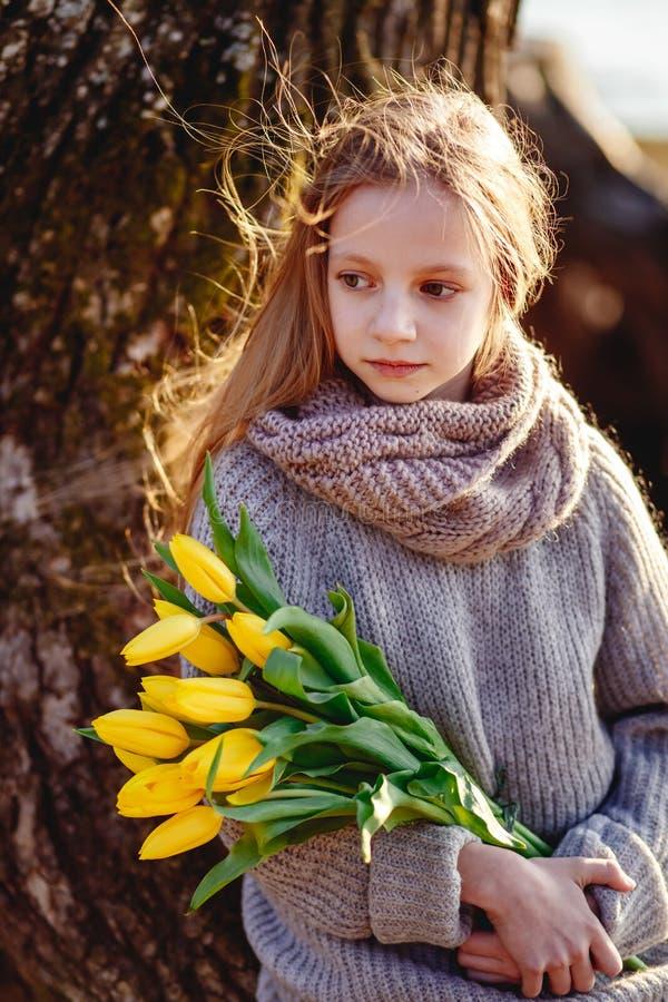 En flicka med gula tulpan i tidig v?r p? en kall afton n?ra floden arkivbilder