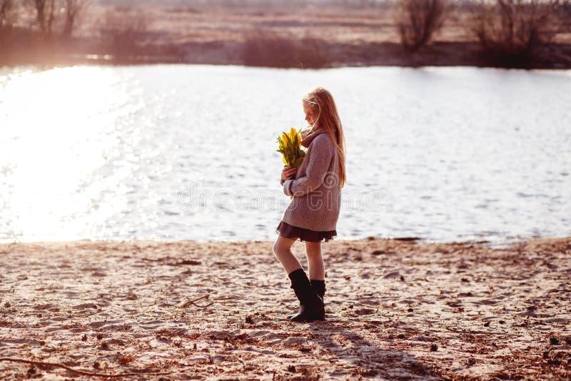 En flicka med gula tulpan i tidig v?r p? en kall afton n?ra floden royaltyfri foto