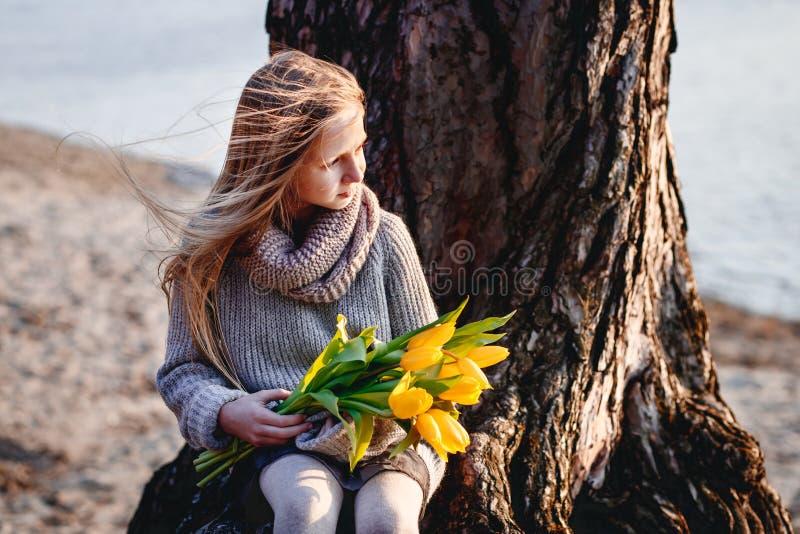 En flicka med gula tulpan i tidig v?r p? en kall afton n?ra floden royaltyfria bilder