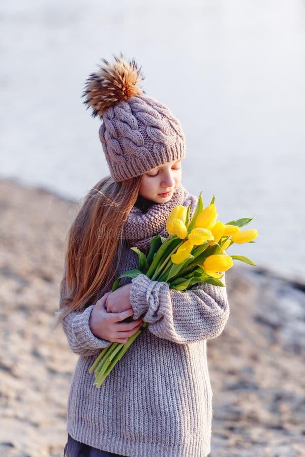 En flicka med gula tulpan i tidig v?r p? en kall afton n?ra floden royaltyfria foton