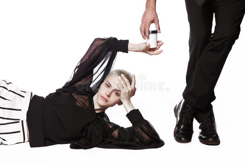 En flicka med en kort frisyr ligger på en vit bakgrund och rymmer en kaffekopp som sträcker en mans hand royaltyfri fotografi