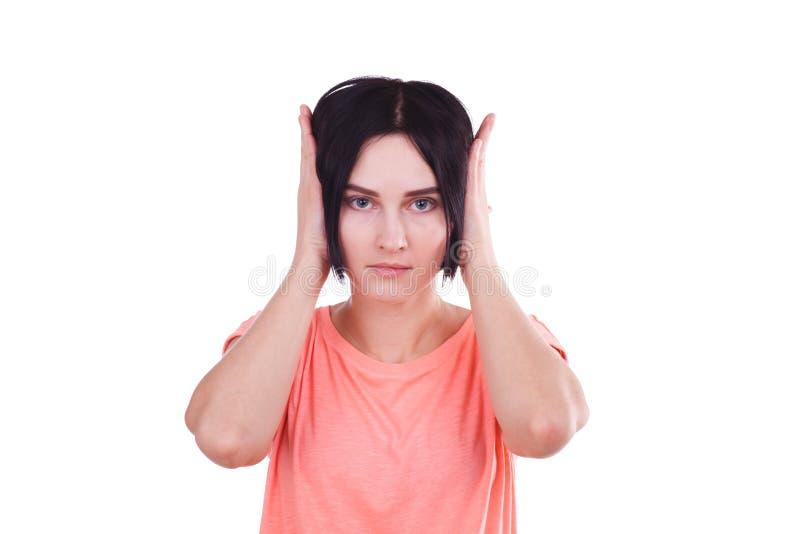 En flicka med kort mörkt hår som täcker henne öron med hennes händer bakgrund isolerad white royaltyfria foton