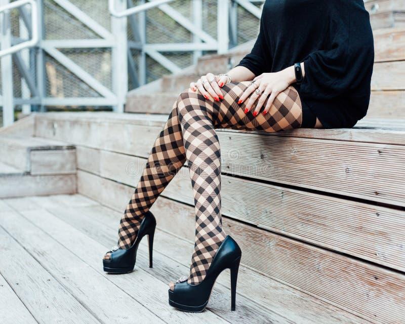 En flicka med långa ben i innegrej, fisknätstrumpor, en kort svart klänning och svart hög-heeled skor sitter i sommaren uppvaktar royaltyfria bilder