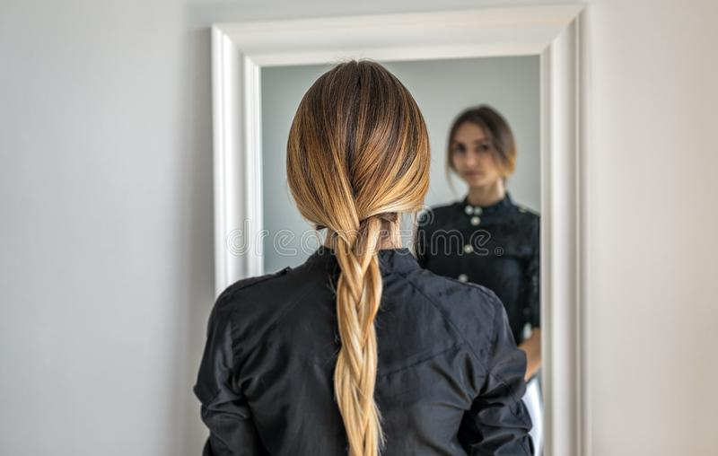 En flicka med långt blont hår som flätas i en flätad tråd, står inomhus mitt emot spegeln royaltyfria foton
