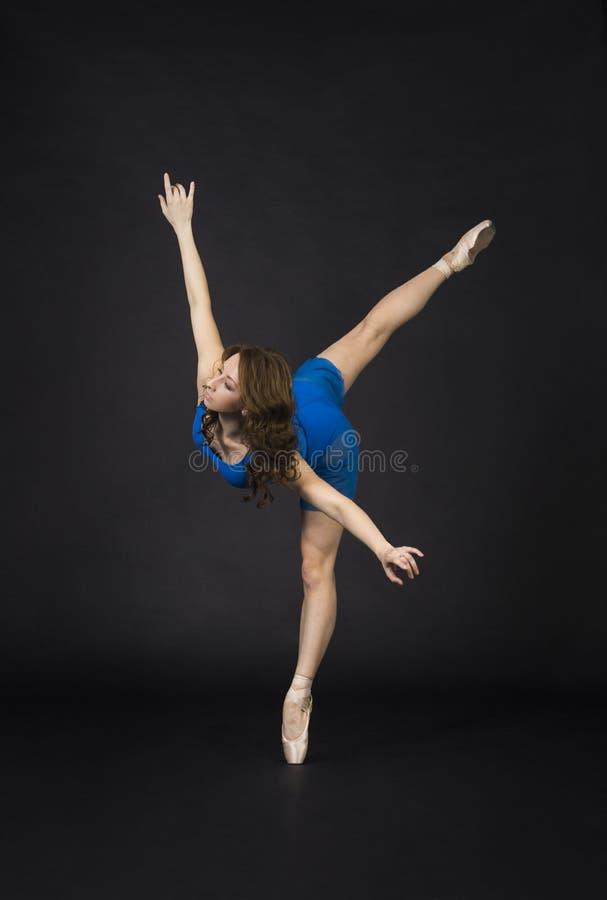 En flicka med långt hår, i en blå klänning och Pointe skor som dansar balett arkivfoto