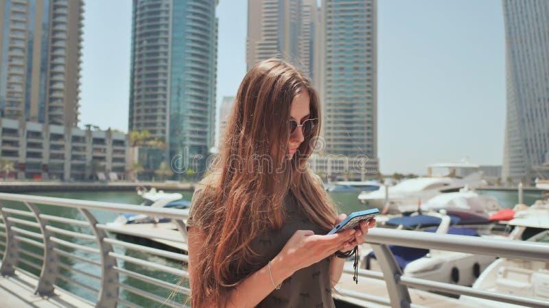 En flicka med långt hår ringer ett meddelande på smartphonen på kajen av den Dubai marina royaltyfri foto