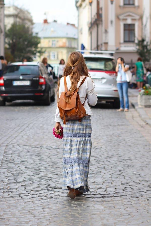 En flicka med långt löst hår går i härlig hippiestilkläder längs de forntida gatorna av en medeltida stad turist- barn royaltyfri bild