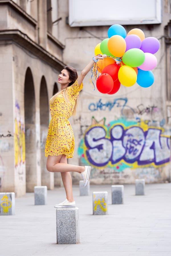 En flicka med många ballons i hand fotografering för bildbyråer