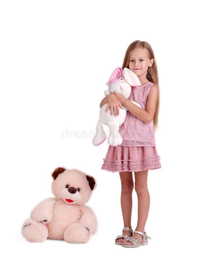 En flicka med en mjuk leksak som isoleras på en vit bakgrund Ett barn som kramar en kaninleksak En stor nallebjörn nära en unge arkivfoton