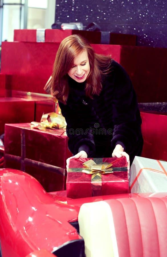 En flicka med rött hår rymmer en ask med en gåva, som ligger på en röd bil Begreppet av det festliga lynnet och trevliga gåvor royaltyfria foton
