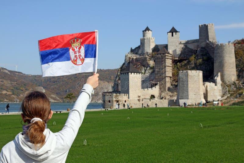 En flicka med en serbisk flagga ser den Golubac fästningen fotografering för bildbyråer